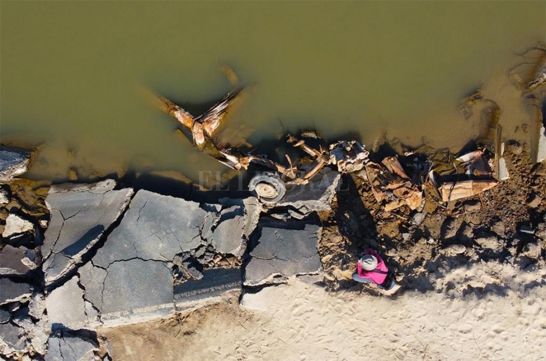 El esqueleto de la camioneta y el reportero gráfico del diario El Litoral in situ, en el instante de la captura histórica de los vestigios.